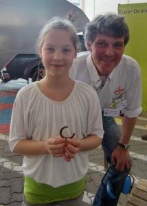 Eine junge Schmiedin zeigt ihr selbst geschmiedetes Hufeisen.